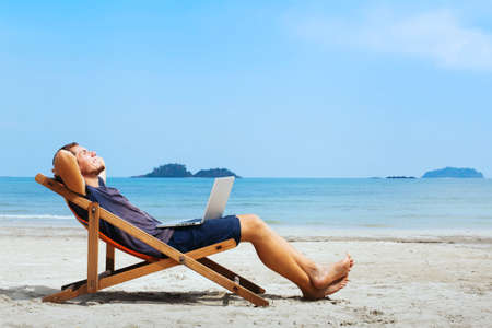 Photo pour smiling businessman with computer relaxing on the beach - image libre de droit