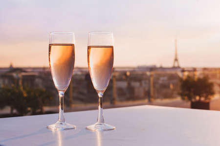Foto de two glasses of champagne at rooftop restaurant with view of Eiffel Tower and Paris skyline, luxury romantic dinner for couple - Imagen libre de derechos