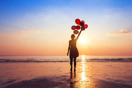 Foto de motivation or hope concept, follow your dream and inspiration, girl with balloons at sunset - Imagen libre de derechos