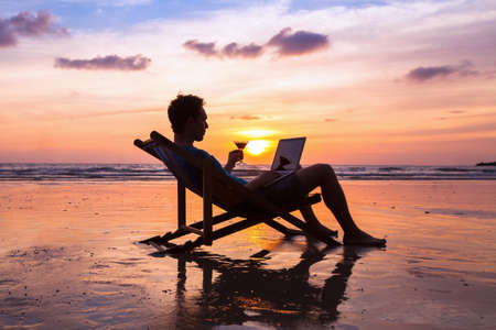 Photo pour silhouette of successful business man reading emails on laptop on the beach at sunset, freelance job concept, work abroad - image libre de droit