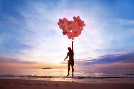 Photo pour love concept, man flying with heart from balloons, fall in love - image libre de droit