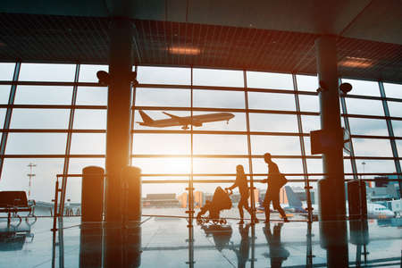 Photo pour people in airport, silhouette of young family with baby traveling by plane - image libre de droit