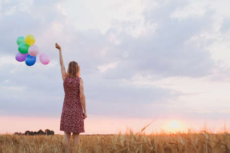 Photo pour hope concept, emotions and feelings, woman with colourful balloons in the field, background - image libre de droit