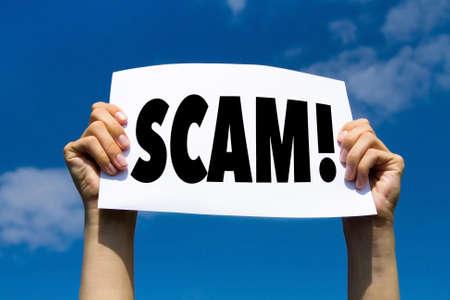 Foto de scam concept sign, hands holding white paper with message text alert - Imagen libre de derechos