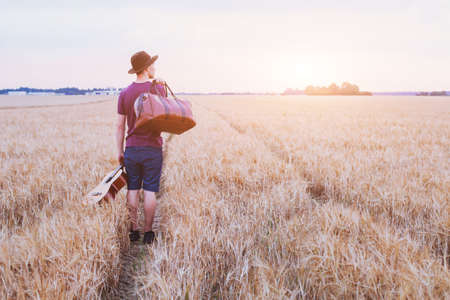 Photo pour young son leaving home, romantic travel background, man with guitar and road bag walking at sunset field - image libre de droit