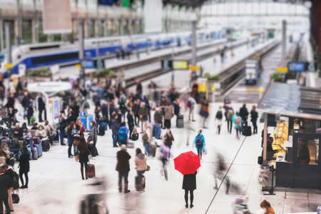 Photo pour woman with red umbrella waiting at train station and blurred people in motion, solitude concept - image libre de droit