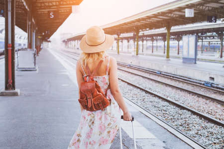 Photo for summer travel, woman with suitcase waiting for  her train on platform of railway station - Royalty Free Image