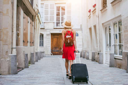 Photo pour travel background, woman tourist walking with suitcase on the street in european city, tourism in Europe - image libre de droit