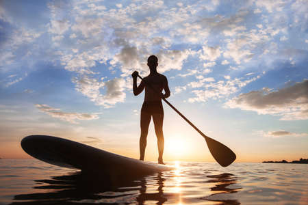 Foto de Paddle standing, silhouette of man on the beach at sunset - Imagen libre de derechos