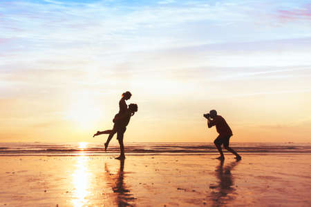 Foto de Photographer working with couple on the beach, professional wedding photography - Imagen libre de derechos