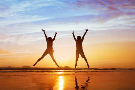 Photo pour Happy couple jumping on the beach at sunset, family summer holidays or honeymoon - image libre de droit