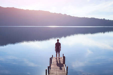 Photo pour Dreamer, silhouette of man standing on the lake wooden pier at sunset, human strength, psychology concept - image libre de droit