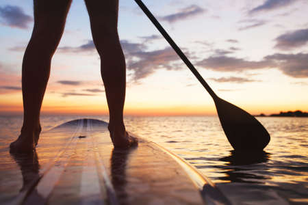 Photo pour paddle board on the beach, close up of standing  legs and paddle - image libre de droit