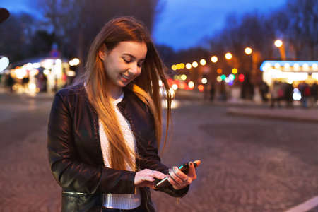 Foto per young woman using smartphone on the street by night and smiling - Immagine Royalty Free