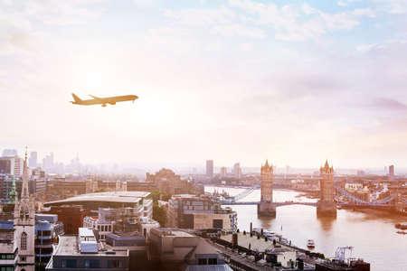 Foto de travel to London by flight, airplane in the sky over Tower Bridge - Imagen libre de derechos