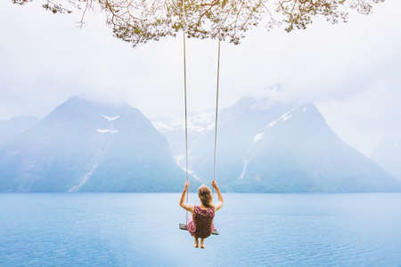 Foto de dream concept, beautiful young woman on the swing in fjord Norway, inspiring landscape - Imagen libre de derechos