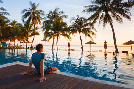 Photo pour happy holidays in beautiful beach hotel at sunset, man sitting near swimming pool and relaxing - image libre de droit