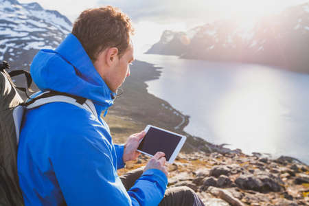 Photo pour traveler backpacker using digital tablet computer outside in mountains, mobile travel application online - image libre de droit