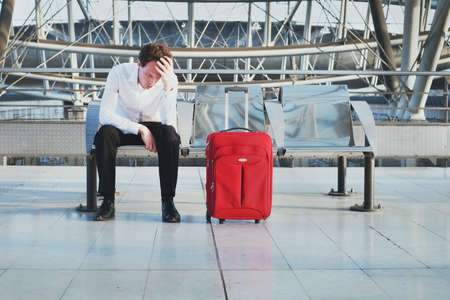 Photo pour flight delay or problem in the airport, tired desperate passenger waiting in the terminal with suitcase - image libre de droit