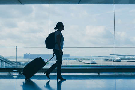 Photo pour departures in airport, silhouette of woman walking with suitcase, travel background with copy space - image libre de droit
