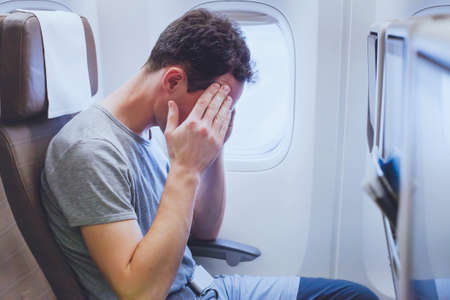 Photo pour headache in the airplane, man passenger afraid and feeling bad during the flight in plane - image libre de droit