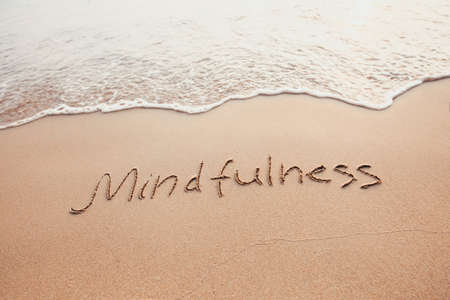 Foto de mindfulness concept, mindful living, text written on the sand of beach - Imagen libre de derechos