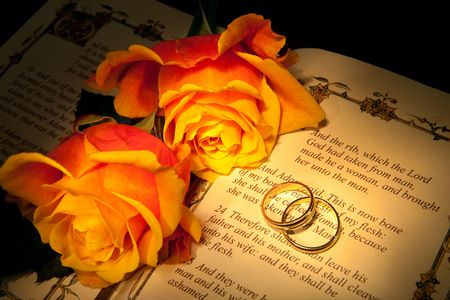 Two wedding rings and roses on a bible with Genesis text - the decorations in the book are copied from a 400 years old bible.
