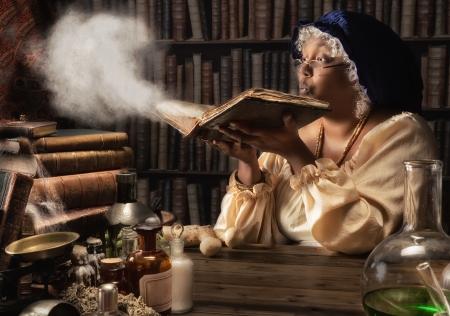 Foto de Medieval alchemist blowing dust off the old books in her laboratory - Imagen libre de derechos