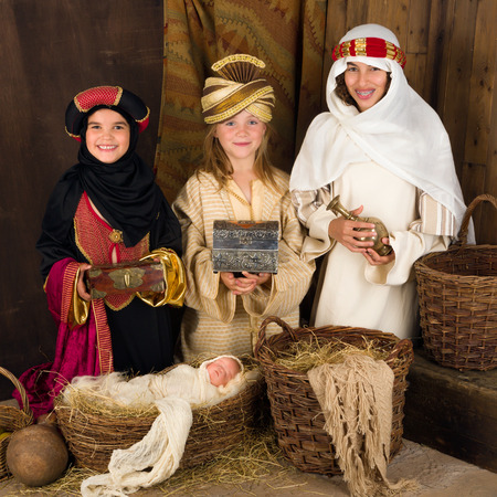 Photo pour Three girls playing as wisemen with a doll in a christmas nativity scene - image libre de droit