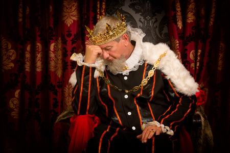 Foto de Pensive and worried king sitting on his throne - Imagen libre de derechos