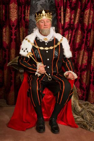 Foto de King in tudor costume sitting on his throne holding his scepter - Imagen libre de derechos