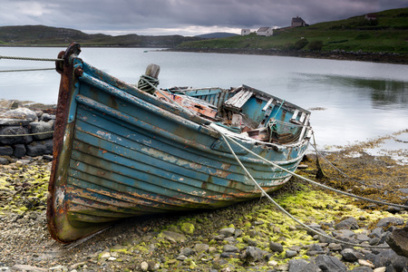 Foto de Weathered fishing boat lying on a rocky beach on the Isle of Lewis, Outer Hebrides, Scotland - Imagen libre de derechos