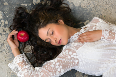 Stunning young woman in white lace dress lying on the floor with a red apple