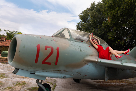 Photo pour Sexy pin-up model in flashy red dress posing on a wing of a WW2 airplane - image libre de droit
