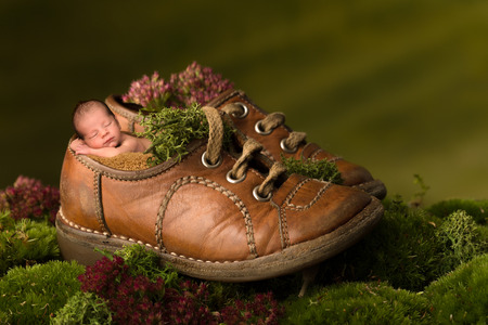 Foto de Newborn baby sleeping in old children shoes - Imagen libre de derechos