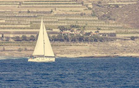 Foto de Lonely sail boat siling past terrace fields. - Imagen libre de derechos