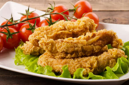 Photo for Golden fried chicken strips in breading with salad and tomatoes on a white plate - Royalty Free Image