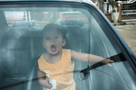 Cheerful boy inside the car enjoy traveling on vacation