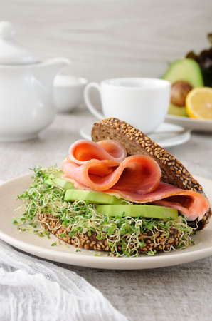 Photo pour Sandwich of rye bread with cereals, slices of ham and avocado with sprouts of sprouted alfalfa. - image libre de droit