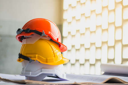 Foto de white, yellow and orange hard safety, helmet hat for safety project of workman or engineer on desk and construction plans with on blueprints - Imagen libre de derechos