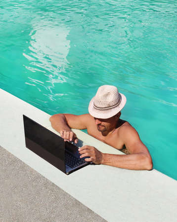 Foto de beautiful man with laptop by the pool - Imagen libre de derechos