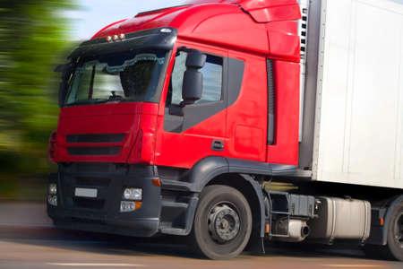 Foto de truck with red cabin goes on road - Imagen libre de derechos