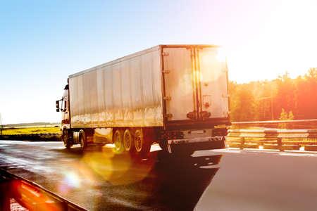 Photo pour big truck goes on the highway to sunrise - image libre de droit