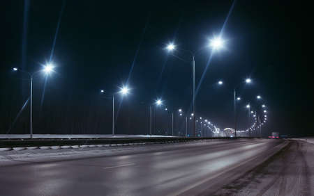 Foto de winter highway at night shined with lamps - Imagen libre de derechos