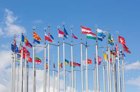 Foto de Flags of European states on flagpoles against the background of a cloudy sky. - Imagen libre de derechos