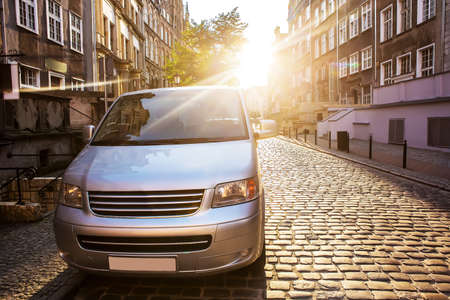 Photo pour Minivan in the historic center of the city in the morning sun - image libre de droit