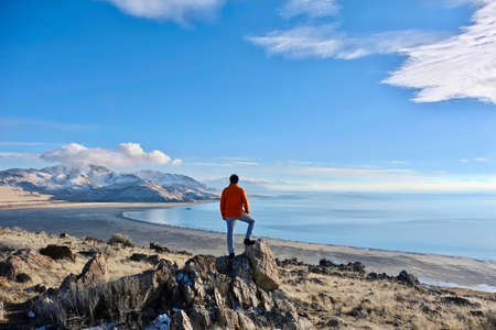Photo for Travelling to Great Salt Lake and Antelope Island in a winter day.  Man hiker on a cliff abover the lake enjoying the scenic views. Salt Lake City. Antelope Island State Park. Utah. United States. - Royalty Free Image