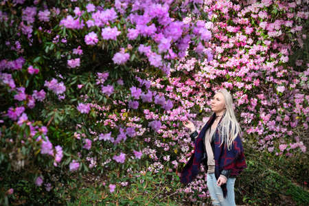 Photo pour Beautiful blond woman in rhododendron garden. Pink and purple rhododendron flowers in full bloom in Queen Elizabeth Garden. Vancouver. British Columbia. Canada. - image libre de droit