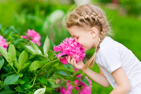 Foto de Beautiful blond little girl with long hair smelling flower - Imagen libre de derechos
