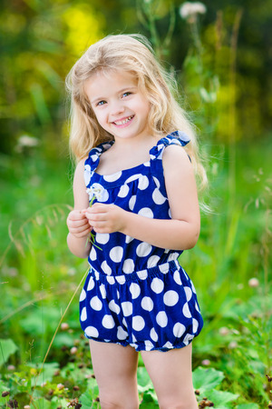 Beautiful smiling little girl with long blond curly hair and flower in her hands. Outdoor full-length portrait in summer park on bright sunny day. Child in green grass field.
